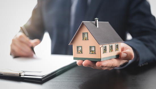 Real estate agent is holding a house model. Buy, loan for a house