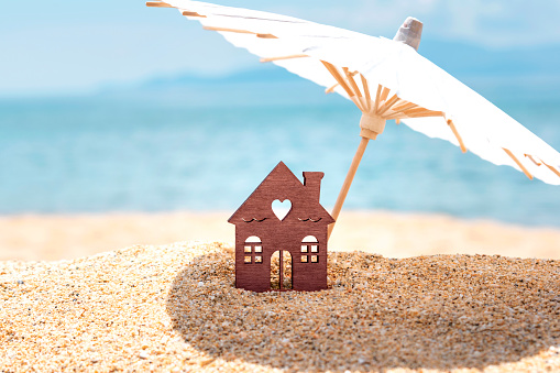 Miniature house and umbrella on beach, blue sea and sky on blurred background. Real estate, sale or property investment concept. Symbol of dream home for family. Copy space